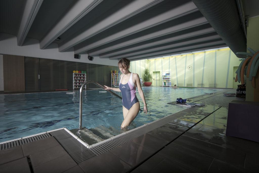 Ragazza esce dalla piscina del Campus Varese con costume Robe di Kappa. Piscina, swimmingpool, fotografia commerciale e di architettura Varese